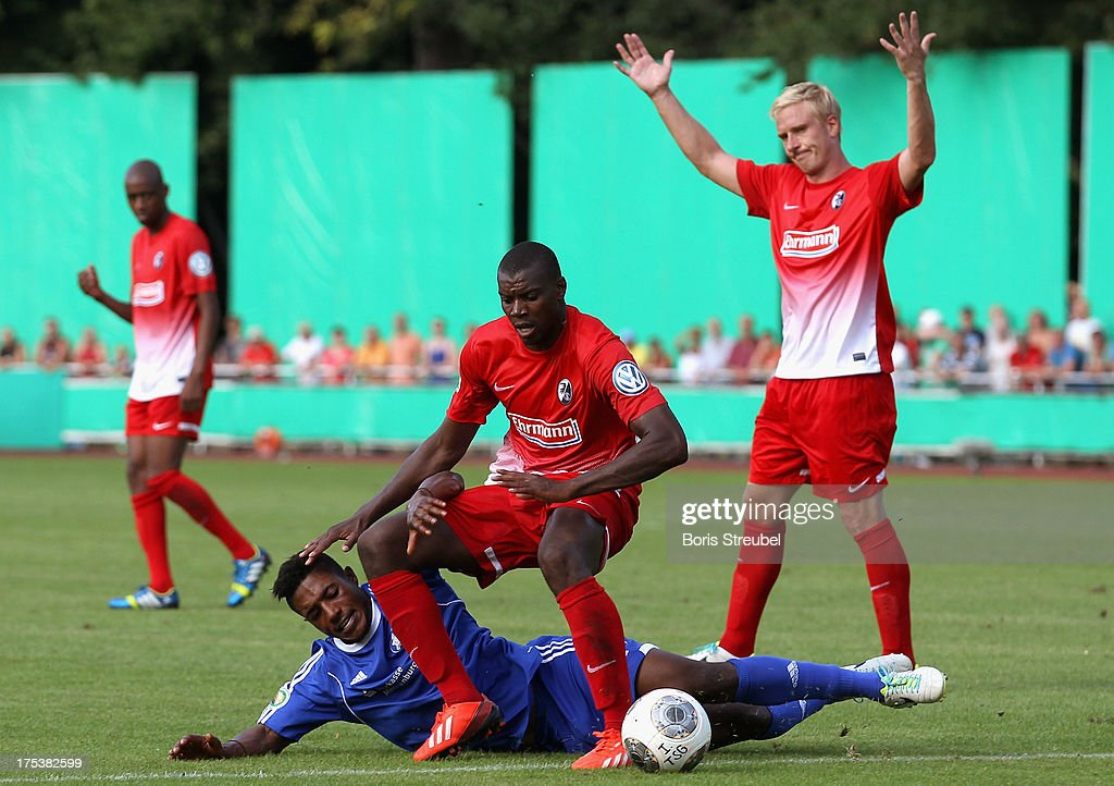 Abiola Collins Folarin (2nd L) of Neustrelitz challenges Karim Guede (C) of Freiburg during the DFB Cup first round match between TSG Neustrelitz and SC Freiburg at Parkstadion on August 3, 2013 in Neustrelitz, Germany.