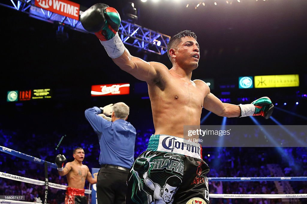 Abner Mares celebrates after defeating Daniel Ponce de Leon as Jay Nady ends the fight in the ninth round in their WBC featherweight title bout at the MGM Grand Garden Arena on May 4, 2013 in Las Vegas, Nevada.