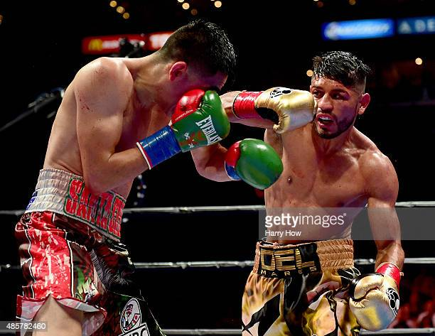 Abner Mares of Mexico takes a punch from Leo Santa Cruz in the 11th round during the WBC diamond featherweight and WBA featherweight championship...