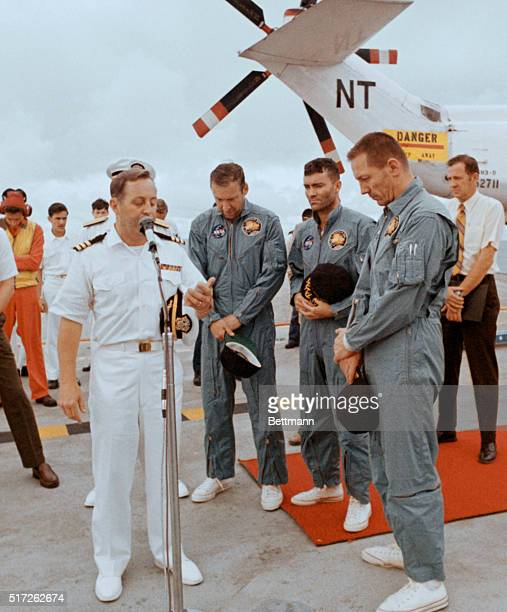 Aboard The Iwo Jima Apollo 13 astronauts James Lovell Fred Haise and John Swigert bow heads in a prayer offered by Navy Chaplain Lt Commander Phillip...