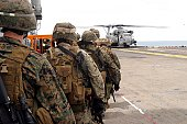 Aboard the USS Essex Marines and sailors progress to board a CH-53E Super Stallion helicopter of Marine Medium Helicopter Squadron 265 (Reinforced) to fast-rope onto the flight deck from a rope here November 15.