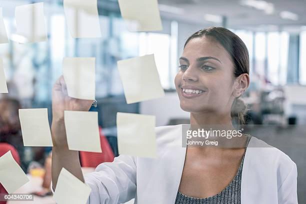 Aboriginal Australian businesswoman smiling, using sticky notes