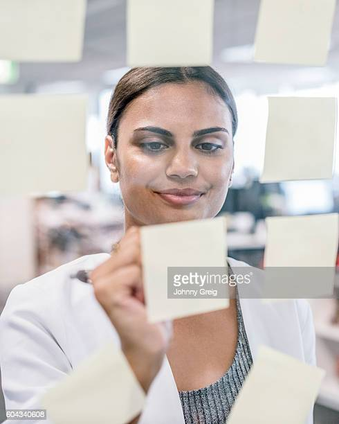 Aboriginal Australian businesswoman sticking notes on window