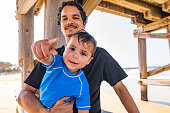Young indigenous Australian father and son playing at the beach