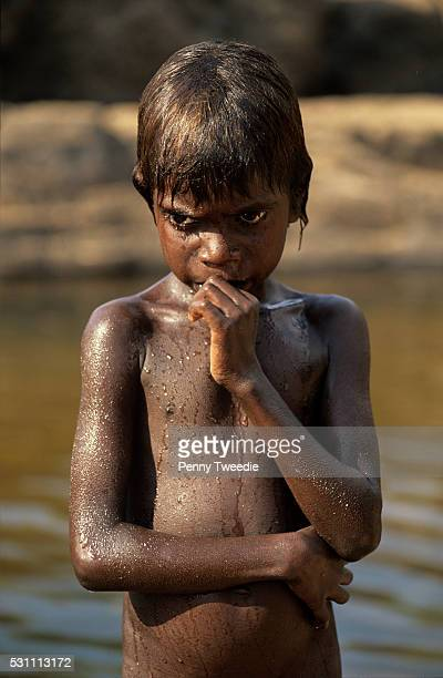 Aboriginal boy Romeo at his grandmother's dreaming site Kubumi waterhole central Arnhem Land