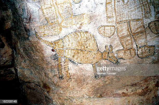 Aboriginal cave painting of men smoking pipes and a Thylacine a now extinct marsupial wolf more commonly known as Tasmanian tiger Noticeable are the...
