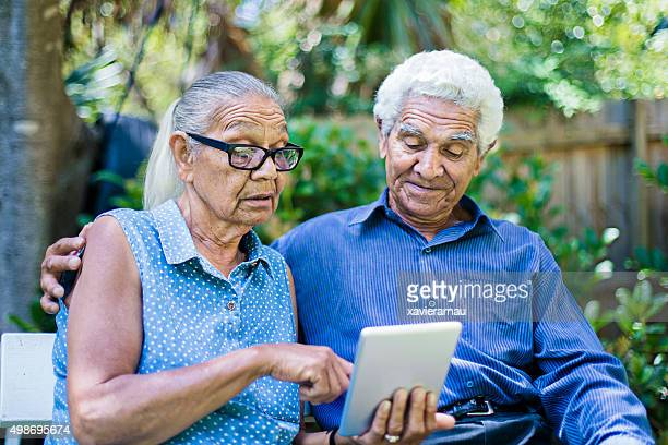 Aboriginal couple using the digital tablet in the garden