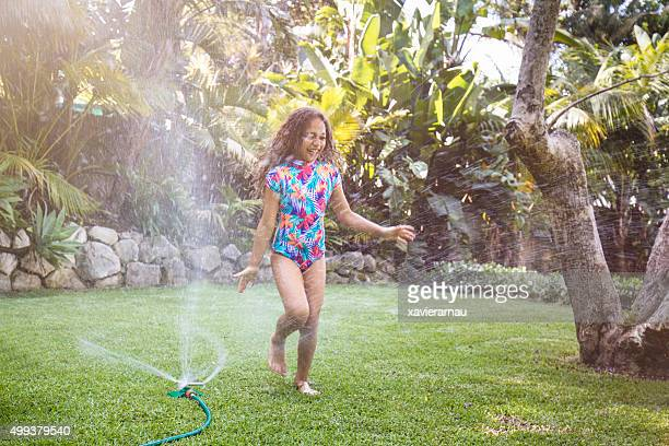 Aboriginal girl jumping over water sprinkler in garden