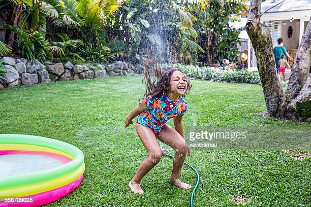 Aboriginal girl jumping over water sprinkler in the back garden
