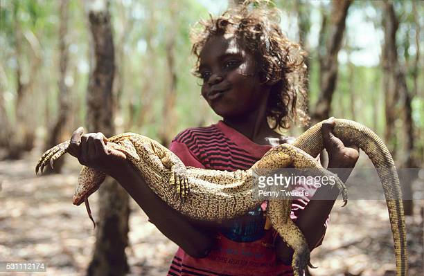 Aboriginal girl Valerie carries a large goanna her brother just caught on a hunting expedition near Ramingining Arnhem land