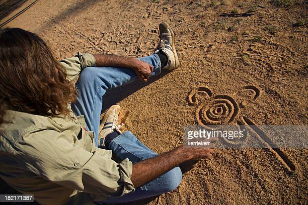 Aboriginal man drawing in the dirt