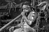 Portrait of one   Yirrganydji Aboriginal man play Aboriginal music on didgeridoo, instrument during Aboriginal culture show in Queensland, Australia.(BW)