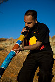 A young Aboriginal man playing a colourful painted didgeridoo in the outback of Australia.