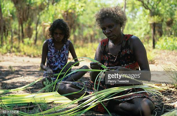 Aboriginal women splitting pandanus for weaving into mats and baskets Arnhem Land This is women's business and currently a way that they can earn a...