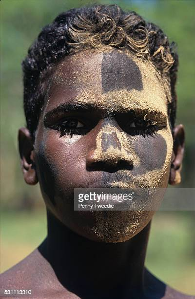 Aboriginal young man Jasper has painted himself up with charcoal and yellow ochre for fun Ramingining Arnham Land he says 'always looking for colou...