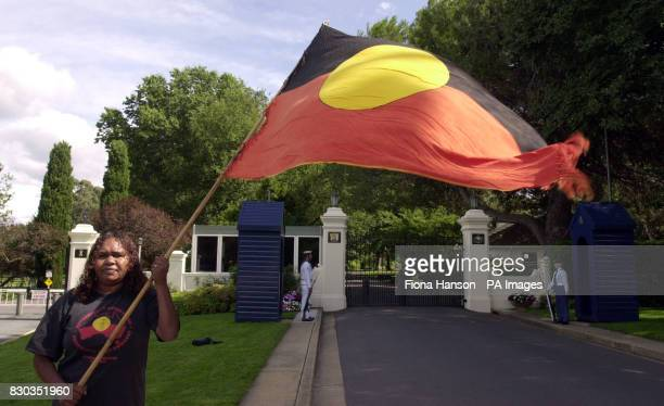Aborigine Donna Gibbs waves the Aboriginal flag outside Government House in Canberra while the Queen who is staying there met Australian Prime...