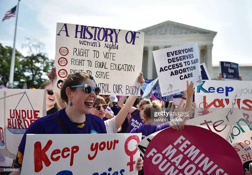Abortion rights activists cheer after the US Supreme Court struck down a Texas law placing restrictions on abortion clinics, outside of the Supreme Court on June 27, 2016 in Washington, DC. In a case with far-reaching implications for millions of women across the United States, the court ruled 5-3 to strike down measures which activists say have forced more than half of Texas's abortion clinics to close. / AFP / MANDEL