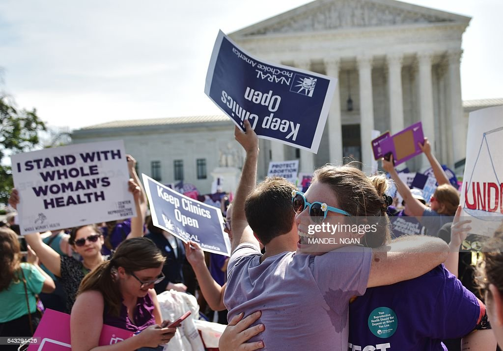 Abortion rights activists embrace after the US Supreme Court struck down a Texas law placing restrictions on abortion clinics, outside of the Supreme Court on June 27, 2016 in Washington, DC. In a case with far-reaching implications for millions of women across the United States, the court ruled 5-3 to strike down measures which activists say have forced more than half of Texas's abortion clinics to close. / AFP / MANDEL