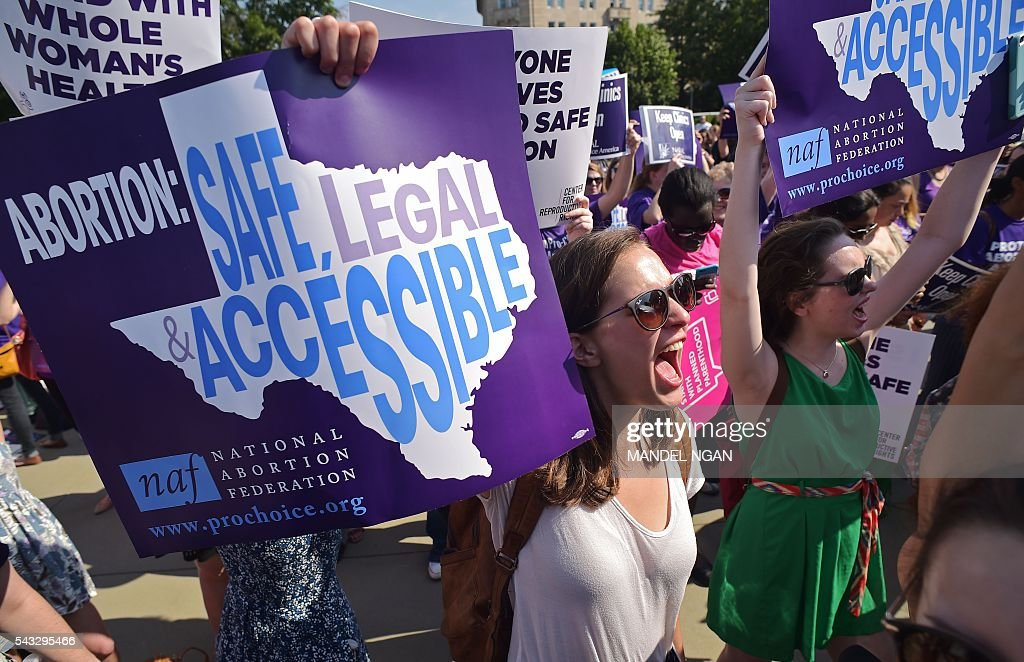 Abortion rights activists hold placards and chant outside of the US Supreme Court ahead of a ruling on abortion clinic restrictions on June 27, 2016 in Washington, DC. In a case with far-reaching implications for millions of women across the United States, the court ruled 5-3 to strike down measures which activists say have forced more than half of Texas's abortion clinics to close. / AFP / MANDEL