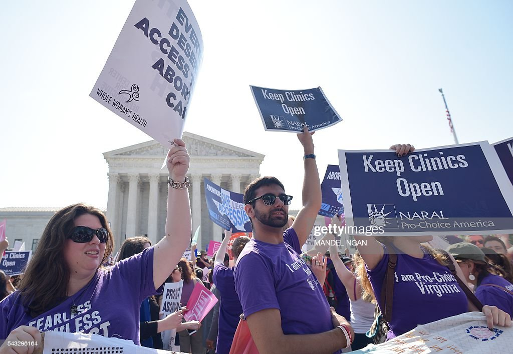 Abortion rights activists hold placards outside of the US Supreme Court ahead of a ruling on abortion clinic restrictions on June 27, 2016 in Washington, DC. In a case with far-reaching implications for millions of women across the United States, the court ruled 5-3 to strike down measures which activists say have forced more than half of Texas's abortion clinics to close. / AFP / MANDEL
