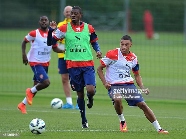 Abou Diaby and Alex OxladeChamberlain of Arsenal during a training session at London Colney on August 30 2014 in St Albans England