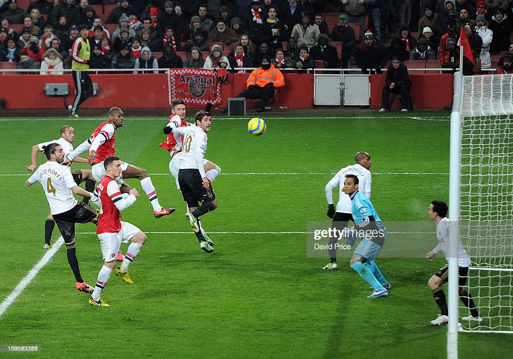 Abou Diaby of Arsenal heads the ball goal wards during the FA Cup Third Round Replay match between Arsenal and Swansea City at the Emirates Stadium on January 16, 2013 in London, England.