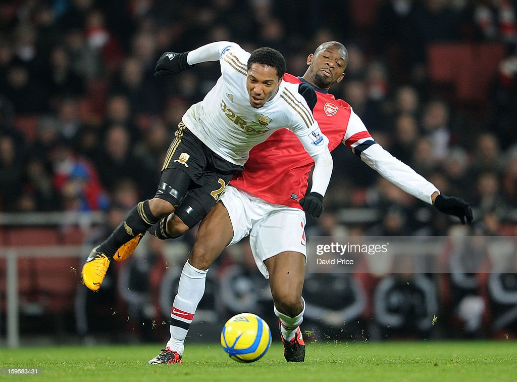 <a gi-track='captionPersonalityLinkClicked' href=/galleries/search?phrase=Abou+Diaby&family=editorial&specificpeople=658258 ng-click='$event.stopPropagation()'>Abou Diaby</a> of Arsenal tackles Jonathan De Guzman of Swansea during the FA Cup Third Round Replay match between Arsenal and Swansea City at the Emirates Stadium on January 16, 2013 in London, England.