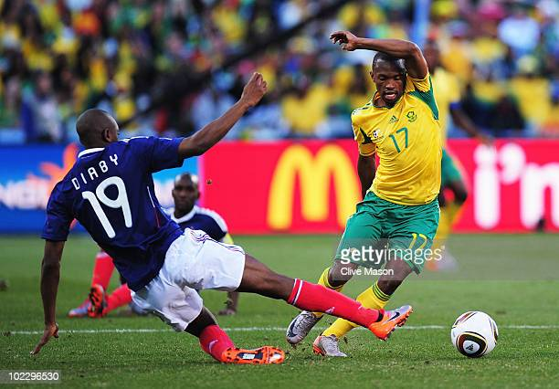 Abou Diaby of France tackles Bernard Parker of South Africa during the 2010 FIFA World Cup South Africa Group A match between France and South Africa...