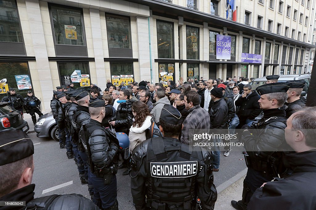 About 150 employees of French auto giant PSA Peugeot Citroen Aulnay face gendarmes outside France's MEDEF employers' association headquarters on March 28, 2013 in Paris, as they gather to protest against the planned closure of their plant.