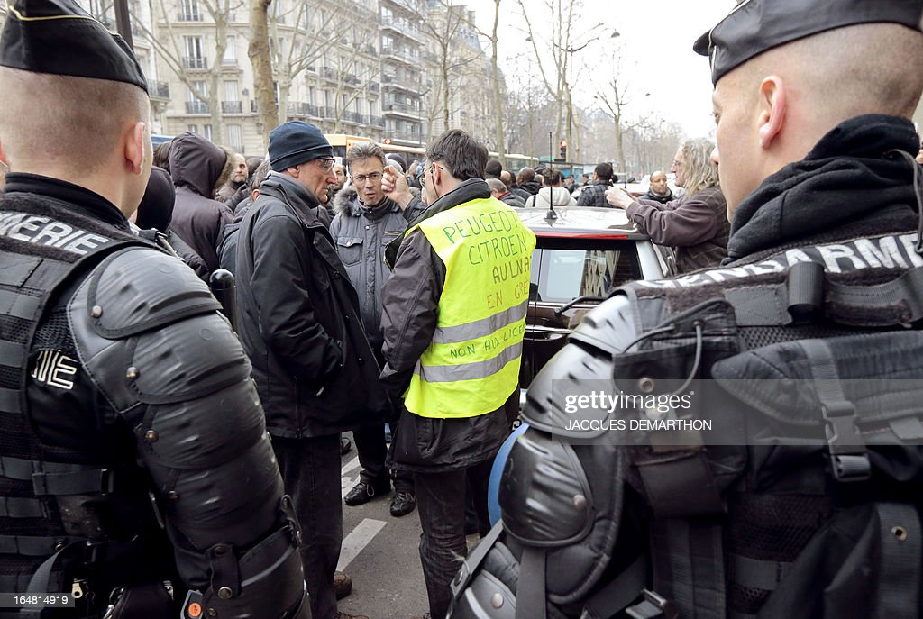 About 150 employees of French auto giant PSA Peugeot Citroen Aulnay are gathered outside France's MEDEF employers' association headquarters on March 28, 2013 in Paris, as they protest against the planned closure of their plant.