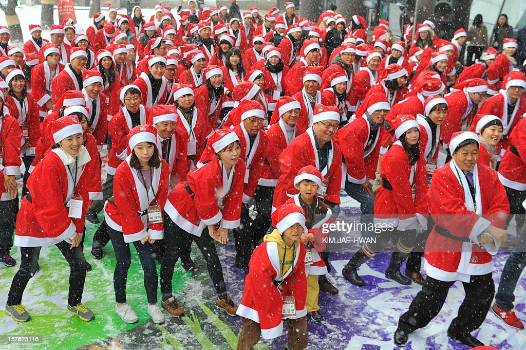 About 200 people clad in Santa Clause outfits imitate South Korean rapper Psy's famous 'Gangnam Style' dance outside offices in Seoul on December 5, 2012. The dance marked the start of a voluntary year-end charity mission to hand out gifts to poor chidren.