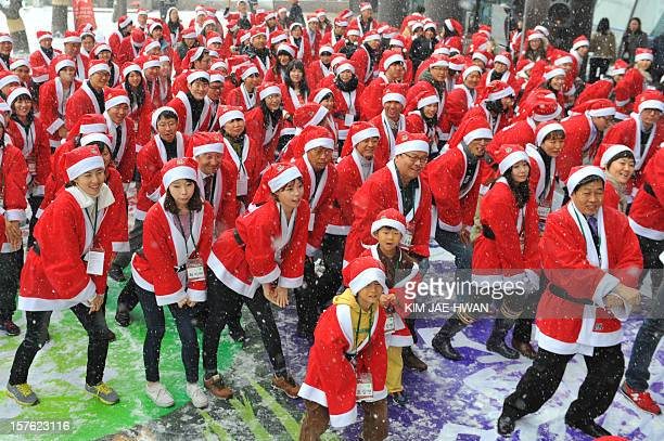 About 200 people clad in Santa Clause outfits imitate South Korean rapper Psy's famous 'Gangnam Style' dance outside offices in Seoul on December 5...
