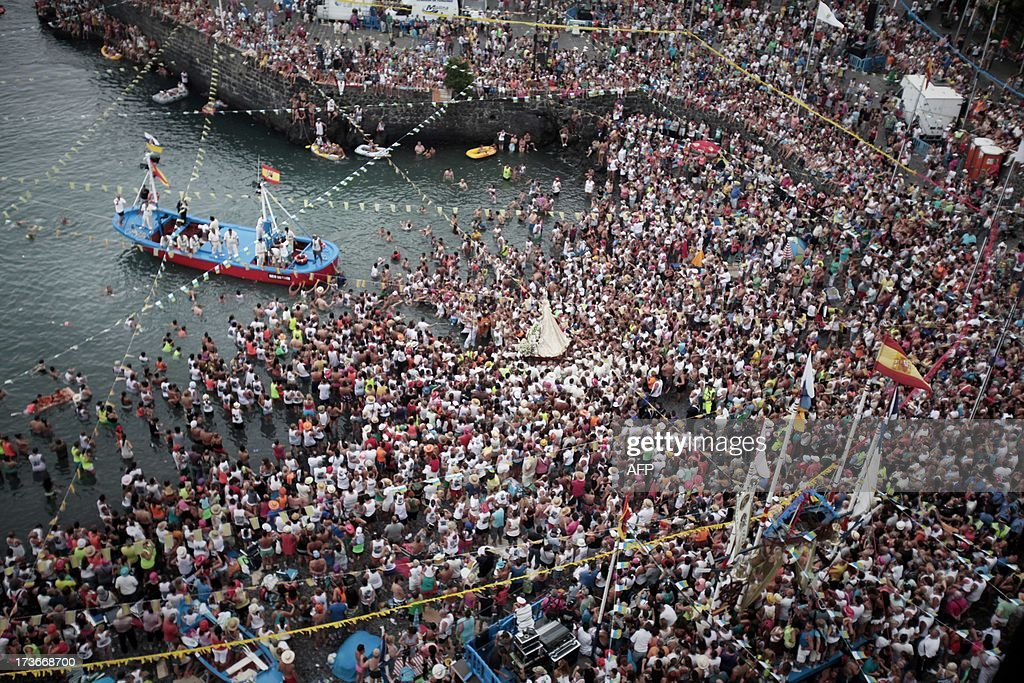 About 25,000 people attend on July 16, 2013, the boat procession of the Virgen del Carmen, patron saint of fishermen, at Puerto de la Cruz on Spain's Canary island of Tenerife. AFP PHOTO / Desiree Martin