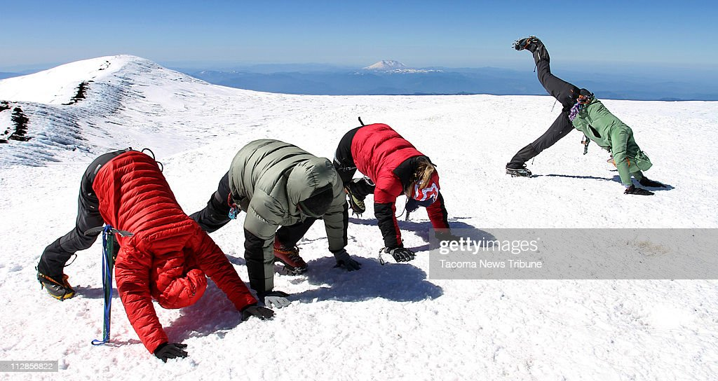 About 5.5 hours after leaving base camp, Lisa Beaudreau, Lynn Dettinger, and Nancy Prichard Bouchard follow Sally Jewell's lead and break into yoga positions on Rainier's summit of 14,411 feet.
