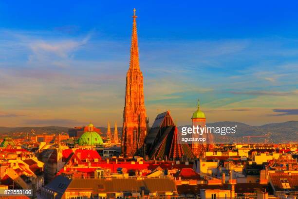 Above Beautiful Vienna Cityscape panorama, with St. Stephen's Cathedral, impressive building architecture and urban skyline at dramatic gold colored sunrise – Vienna , Austria