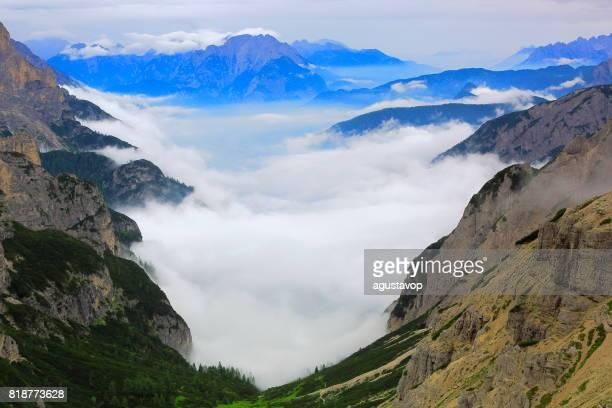 Über idyllische Nebel bedeckt Tre Cime di Lavaredo Pinnacle und Auronzo di Cadore massiv Bergkette, Wolken über dem Pustertal, dramatischer Himmel in der stimmungsvolle Dämmerung, dramatischen Panorama und majestätischen Dolomiten, Italien Tirol Alpen