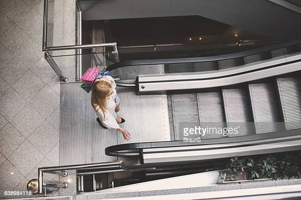 Above view of a woman going on an escalator.