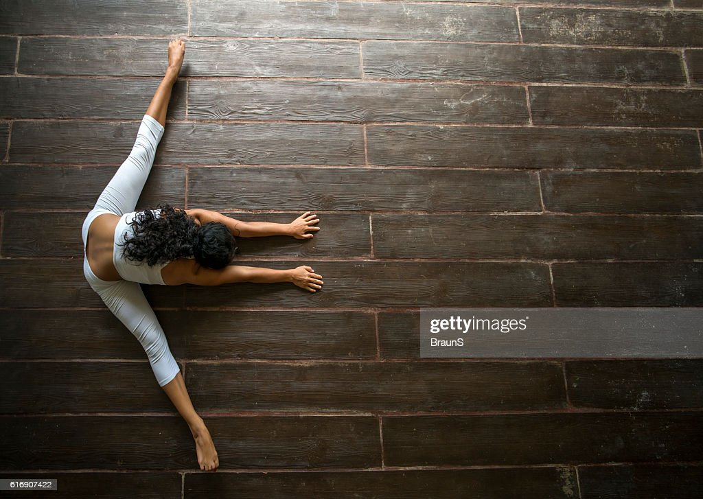 Above view of a woman stretching on wooden floor. : Stock Photo