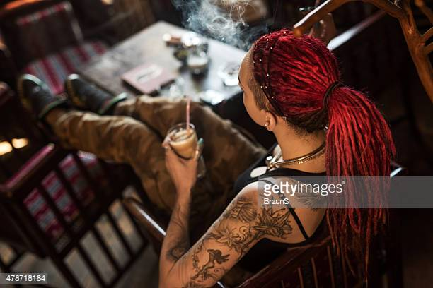 Above view of a woman with dreadlocks in a cafe.