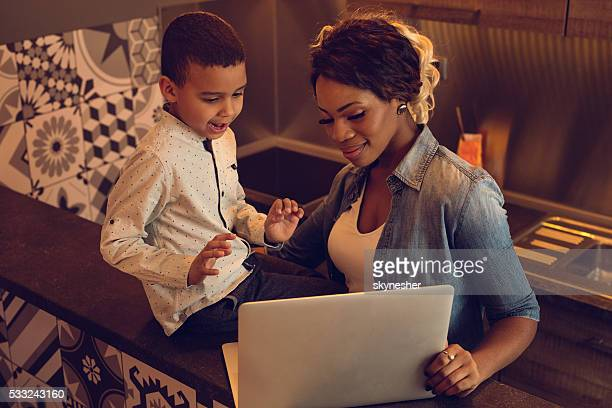 Above view of African American mother and son using laptop.