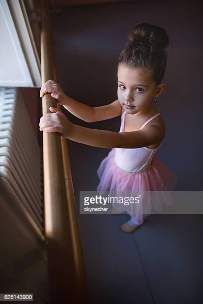 Above view of cute little ballerina looking at camera.