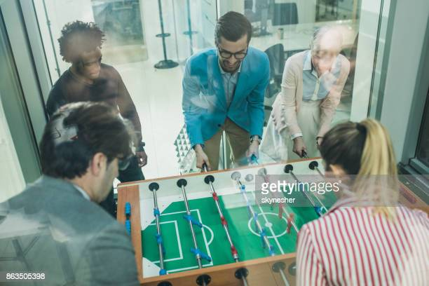 Above view of group of happy business people playing foosball on a break.
