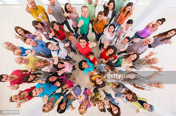 Above view of group of happy people showing thumbs up.