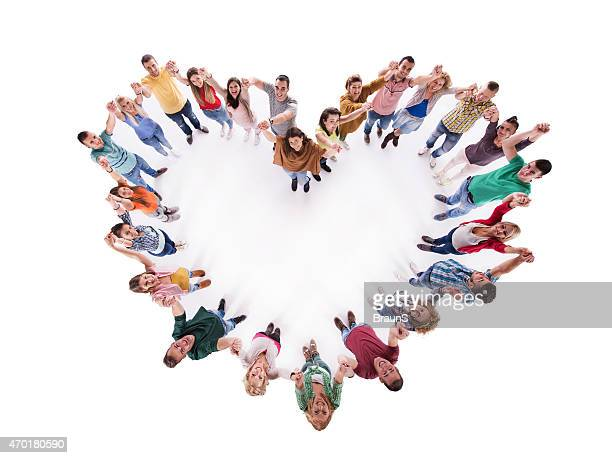 Above view of group of young people making heart shape.