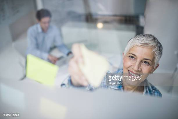 Above view of happy businesswoman making mind map with sticky notes in the office.