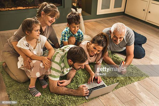 Above view of happy extended family shopping online at home.