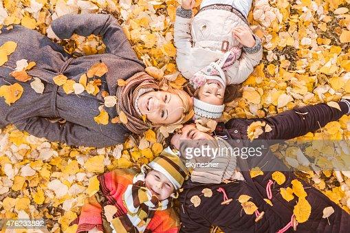 Vista de arriba de happy family lying en otoño las hojas.