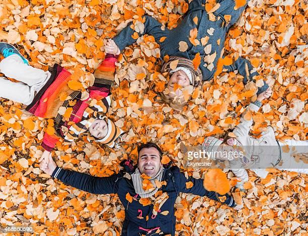 Luftaufnahme von happy family lying in der Blätter.