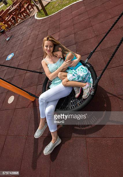 Above view of loving mother and daughter in a swing.