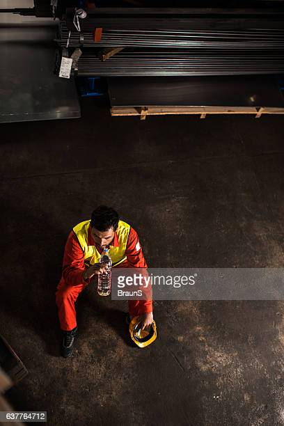 Above view of manual worker on water break in warehouse.